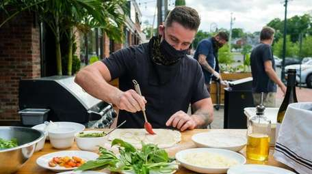 Pizza chef Michael Vigliotti brushes his dough with