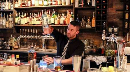 Bartender mixes cocktails behind the bar of Vauxhall