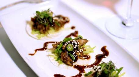 An appetizer of Peking duck is prepared with