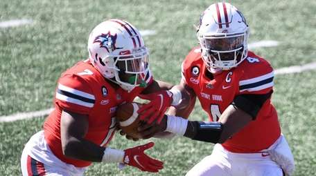 Stony Brook Seawolves quarterback Tyquell Fields hands the