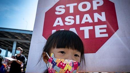 Setauket resident Lucia Yuam, 6, holding a sign