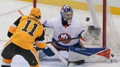 The Penguins' Frederick Gaudreau scores over Islanders goaltender