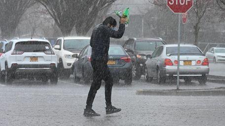 A man walks in the rain outside the