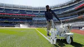 The grounds crew prepares Yankee Stadium for Opening