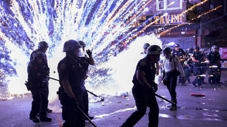 A firework goes off near NYPD cops during