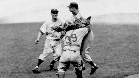 Brooklyn Dodgers pitcher Johnny Podres is lifted by