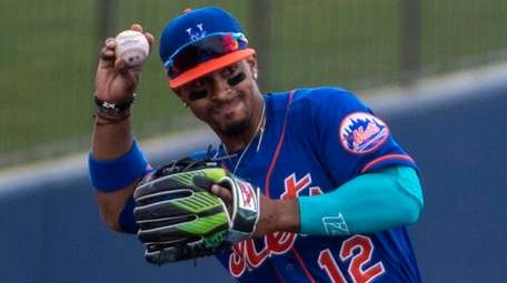 The Mets' Francisco Lindor throws to first during