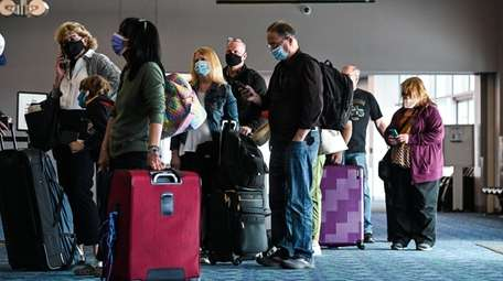 Passengers wait in line at a Frontier Airlines