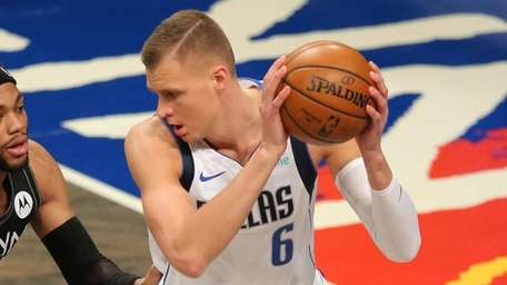 Mavericks center Kristaps Porzingis controls the ball against