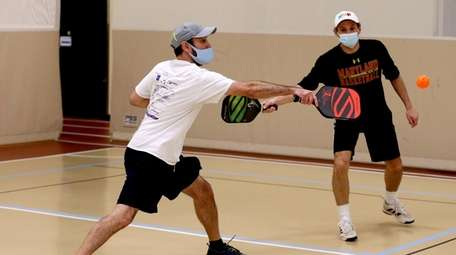 Rich Francisco, left, and Greg Waks play pickleball