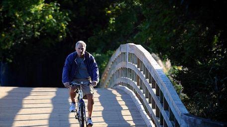 A bike rider crosses a bridge at Sunken
