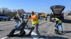 Workers patch potholes along the westbound Long Island