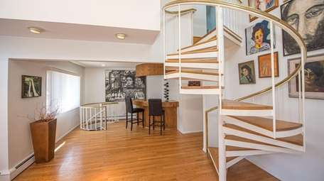 A spiral staircase goes upstairs and another goes