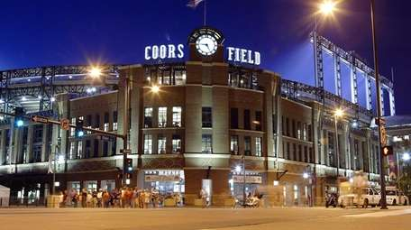 Fans leave the front entrance of Coors Field