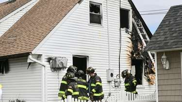 Firefighters examine the scene of a Levittown house