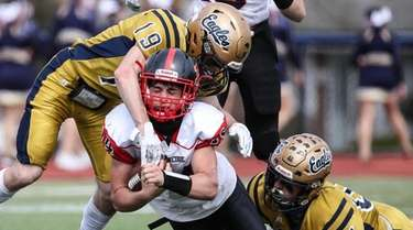 Plainedge quarterback Joe Iadevio (14) gets taken down