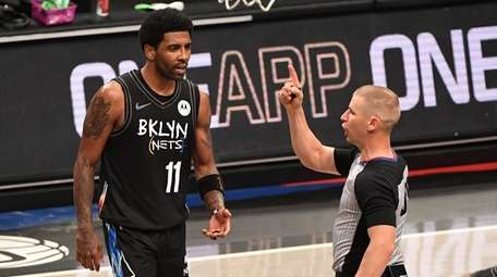 Nets guard Kyrie Irving reacts after he is