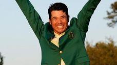 Hideki Matsuyama celebrates after putting on the champion's