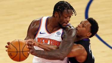 The Knicks' Julius Randle, left, is guarded by