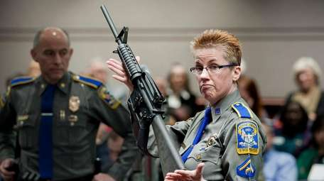 A Bushmaster AR-15 rifle is displayed by a