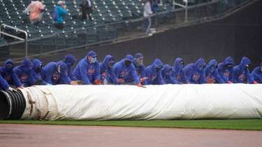 Mets employees roll a tarp over the field
