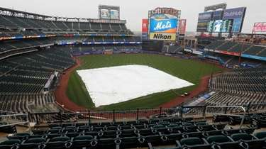 The tarp is seen on the field after