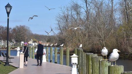 People stroll the RiverWalk along Riverhead's Peconic Riverfront