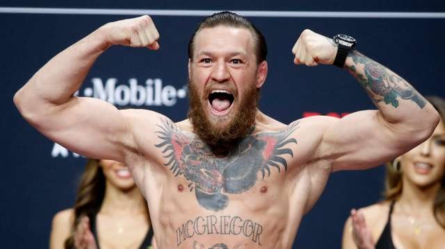 Conor McGregor poses during a ceremonial weigh-in for