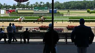 Employees watch a race during the Belmont Stakes