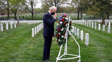 President Joe Biden makes a sign of the