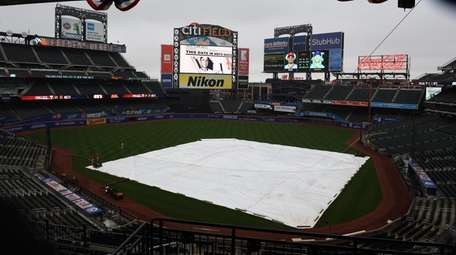 The tarp is on the field before an