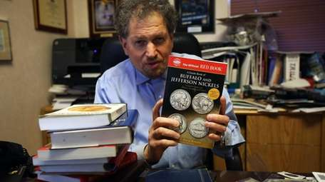 "Dr. David Menchell displays ""The Official Red Book"