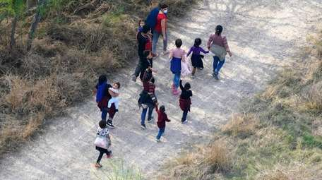 Migrants walk on a dirt road after crossing