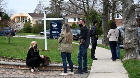 Prospective buyers wait outside an open house in