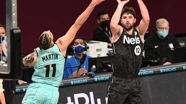 Nets forward Joe Harris shoots from outside defended