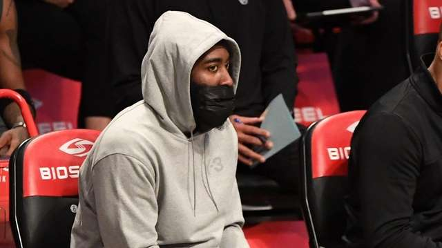 Nets guard James Harden sits on the bench
