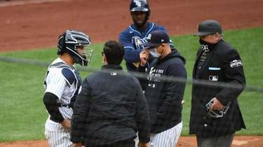 Yankees catcher Gary Sanchez is checked on by