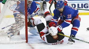 Rangers' Chris Kreider (20) hits New Jersey Devils'