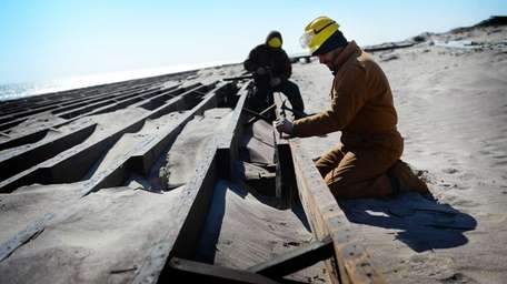Contractors work to rebuild a section of the