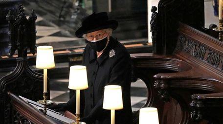 Queen Elizabeth II watches as pallbearers carry the