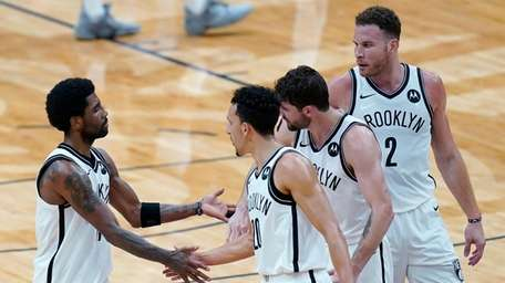 Nets guard Kyrie Irving, left, celebrates with teammates