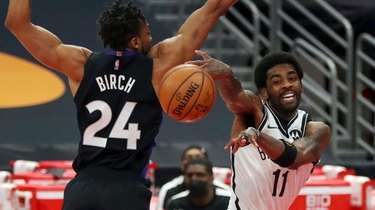 Nets' Kyrie Irving (11) passes around Toronto Raptors'