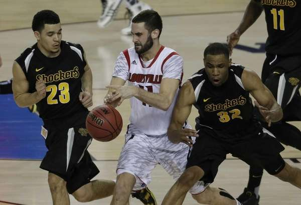 Louisville's Luke Hancock (11) works against Wichita State's