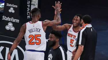 Knicks guard Immanuel Quickley celebrates with forward Reggie