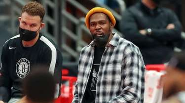 Nets' Kevin Durant, center, sits with Brooklyn Nets'