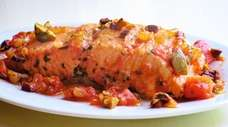 Salmon roasted with onions, tomato, olives, and basil.