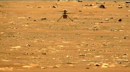 The Mars Ingenuity helicopter hovers above the surface