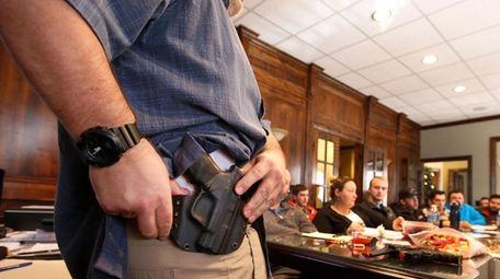 Damon Thueson shows a holster at a gun