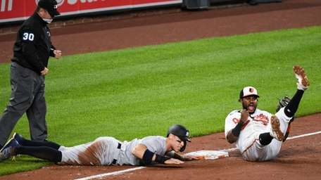 Baltimore Orioles third baseman Maikel Franco, left, reacts