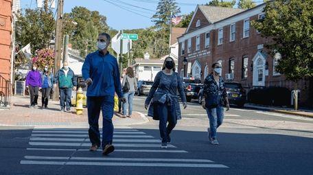 People wearing masks walk in Port Jefferson in